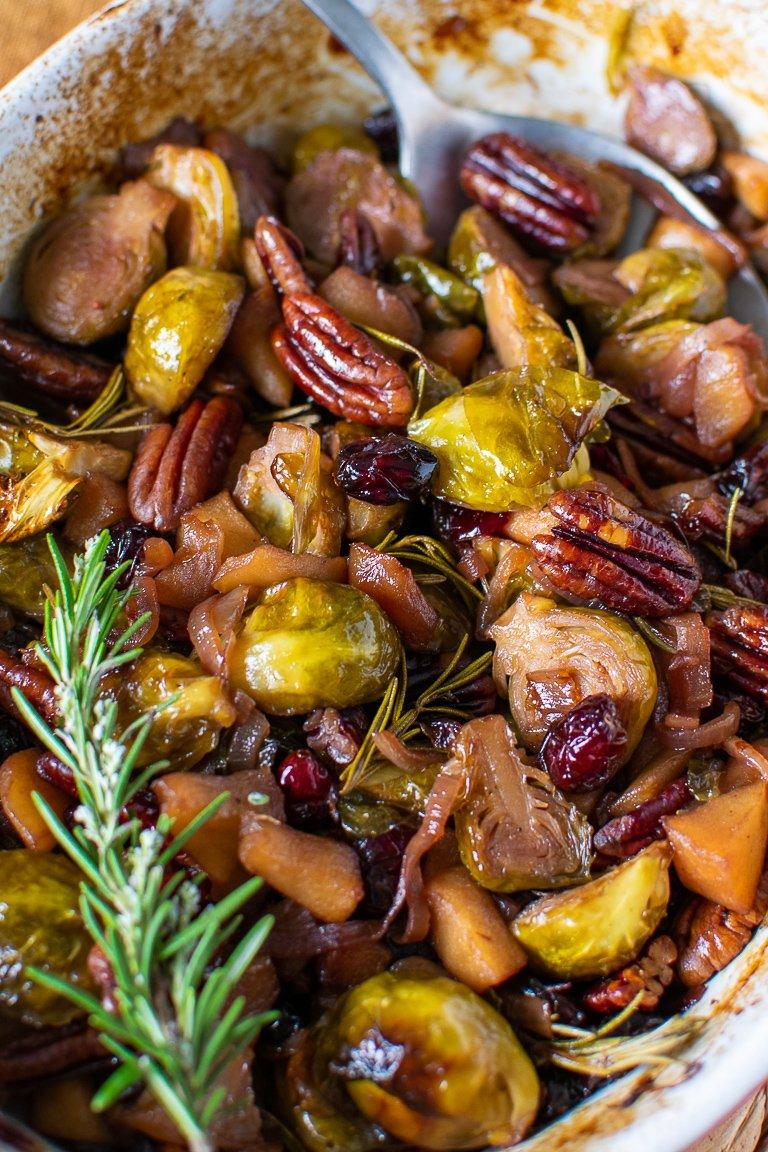 Teglia con cavoletti di Bruxelles, mele, cipolle, mirtilli rossi essicatti e noci. Glassati con sciroppo d'acero e cotti in forno.