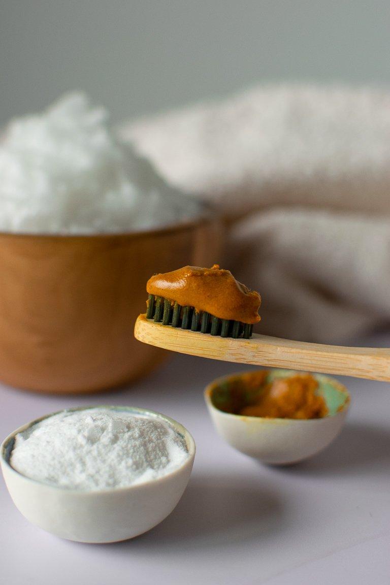 trattamento sbiancante per i denti completamente naturale. spazzolino di bambù con dentifricio arancione fatto con olio di cocco, bicarbonato e curcuma