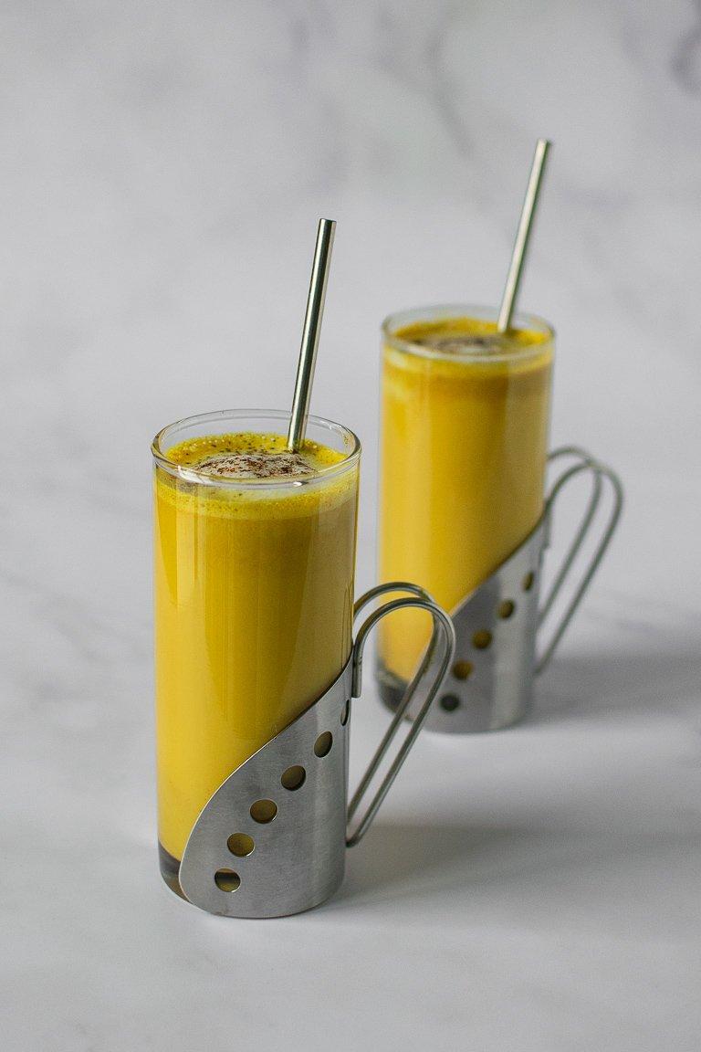 Due tazze in vetro piene di latte dorato alla curcuma