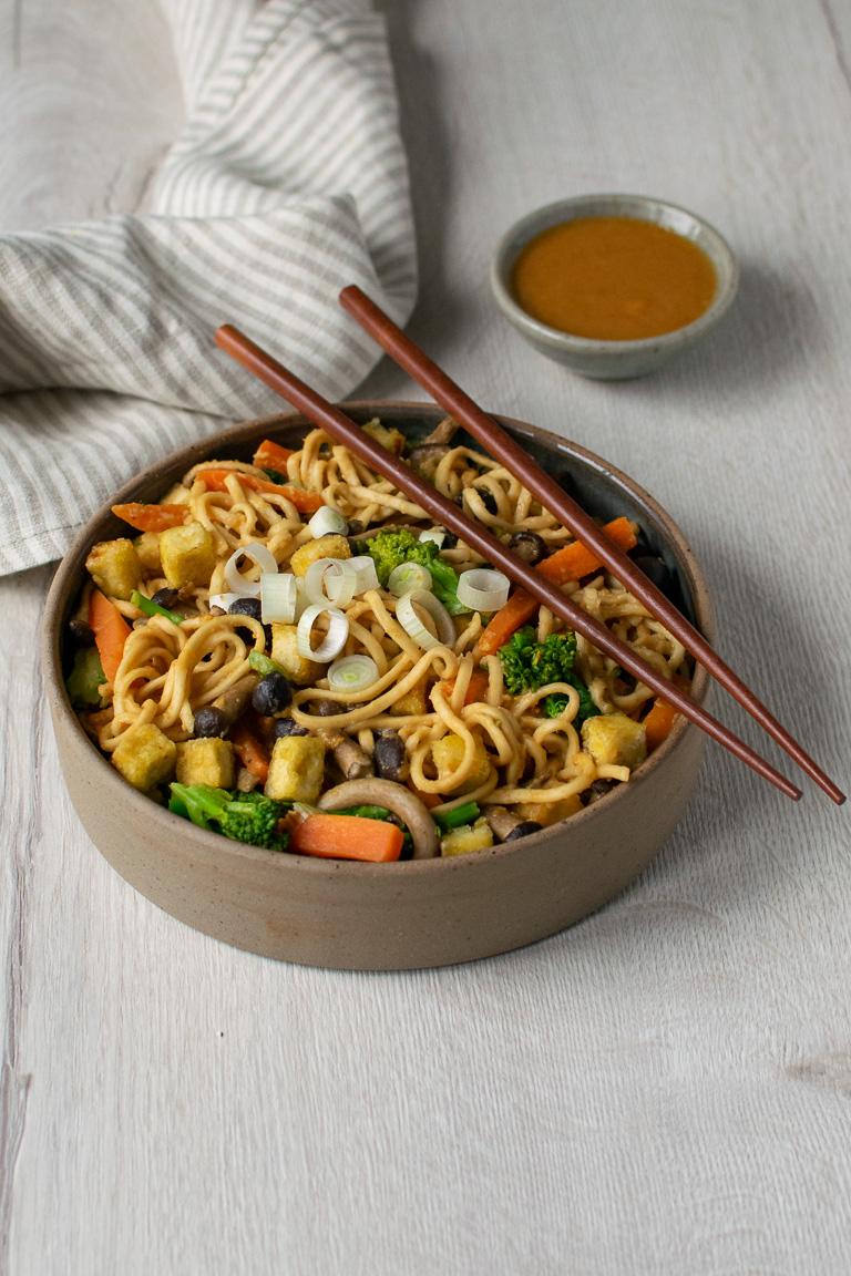ciotola di noodles con verdure, funghi e tofu croccante, bacchette cinesi poggiate sopra e ciotolina con salsa agrodolce