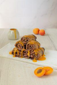 Torretta di crepes al cacao arrotolate e coperte con coulis di albicocche